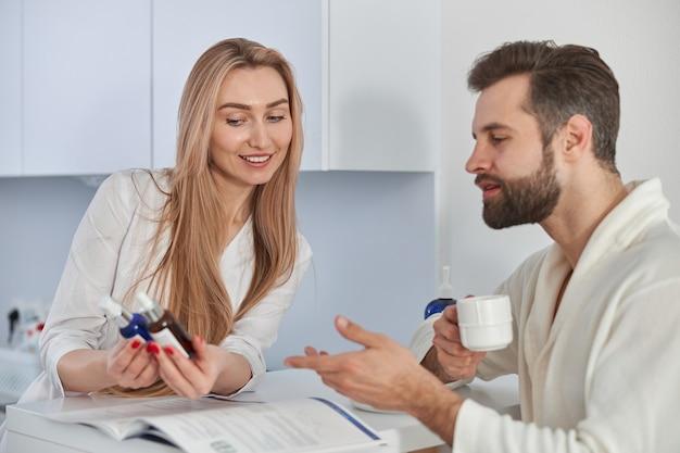Pracownik medyczny konsultuje pacjenta z broszurą i zabiegami kosmetycznymi. cierpliwy młody człowiek stojący w pobliżu recepcji i trzymając herbatę.