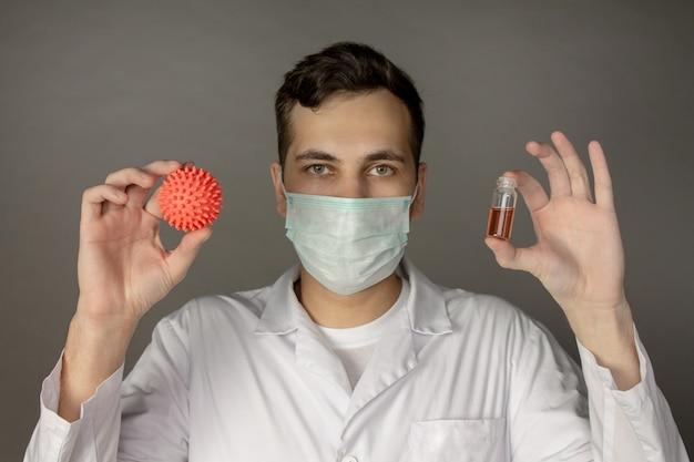 Pracownik medyczny nosi maskę i trzyma model koronawirusa.
