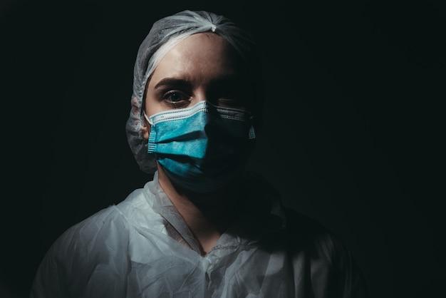 Pracownik medyczny noszący maskę na czarnym tle