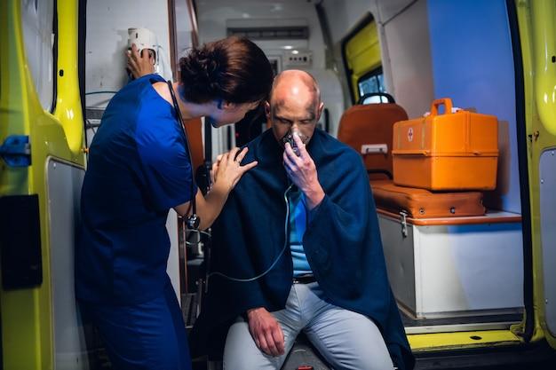 Pracownik medyczny udzielający pomocy psychologicznej mężczyźnie uratowanemu z pożaru