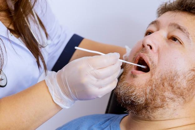 Pracownik medyczny w rękawiczkach ochronnych w celu sprawdzenia wymazu z jamy ustnej mężczyzny pod kątem koronawirusa covid-19 w teście plr