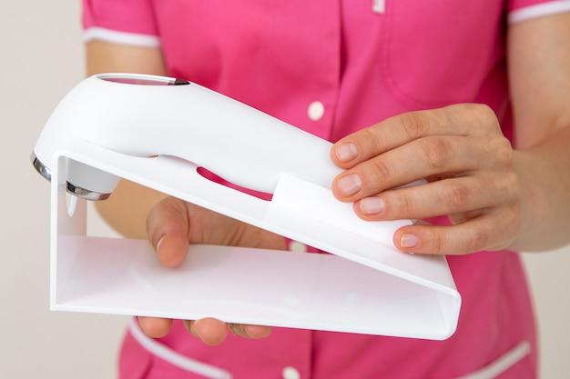 Pracownik medyczny w różowym mundurze trzyma urządzenie laserowe do pielęgnacji skóry twarzy i ciała. młodość i piękno. salony piękności. kosmetyka. dermatologia. zabiegi kosmetyczne. narzędzia kosmetyczki. technologie laserowe