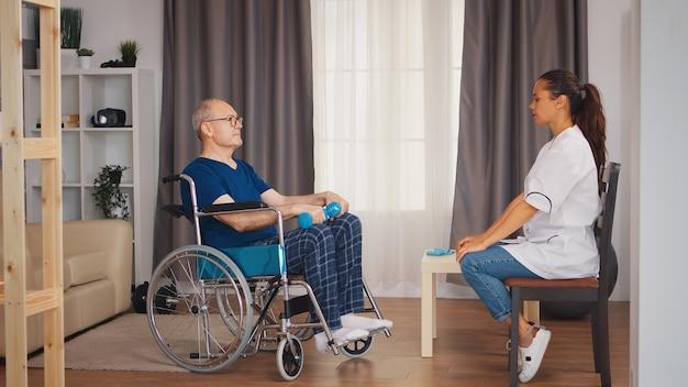 Pracownik medyczny ze starym pacjentem na wózku inwalidzkim robi fizjoterapię. osoba starsza niepełnosprawna niepełnosprawna z pracownikiem socjalnym w okresie rekonwalescencji terapia rehabilitacyjna fizjoterapia służba zdrowia pielęgniarstwo dom spokojnej starości