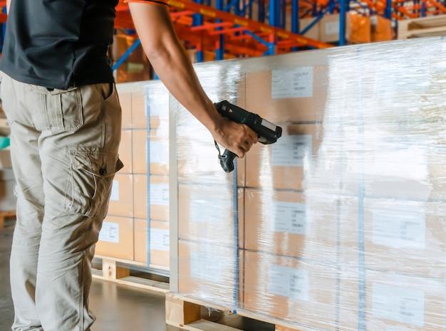 Pracownik mężczyzna ręka trzyma skaner kodów kreskowych ze skanowaniem na palecie ładunkowej w magazynie
