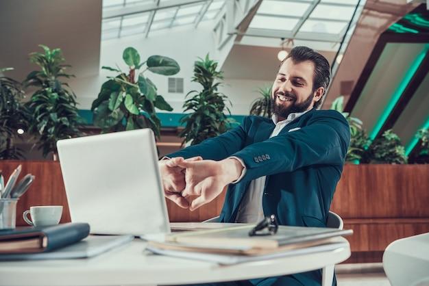 Pracownik mężczyzna w kostiumu ćwiczy rozciąganie ręki w biurze.