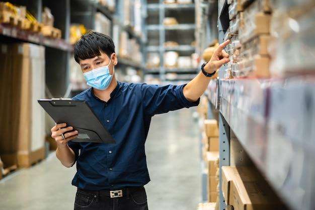 Pracownik mężczyzna z maską medyczną trzymający schowek i sprawdzający zapasy w magazynie podczas pandemii koronawirusa