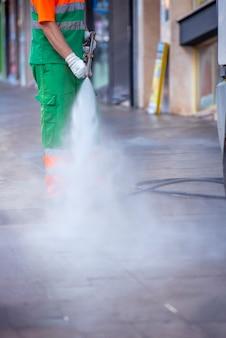 Pracownik miasta z pistoletem ciśnieniowym. czyszczenie ulic i małej architektury w celu zapobiegania covid19, koronawirusowi