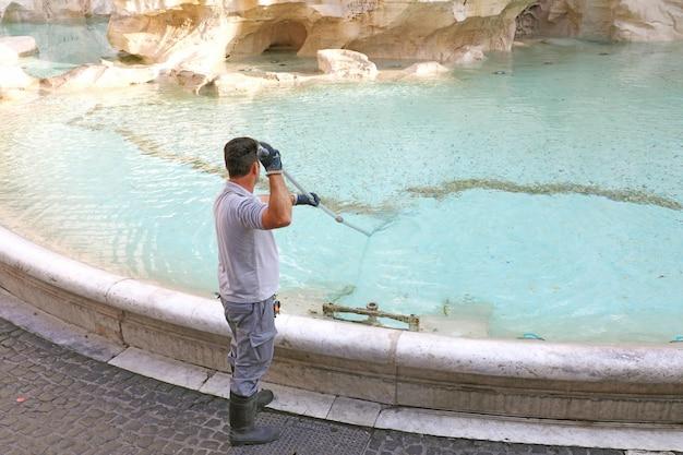 Pracownik miejski zbierający pieniądze z fontanny di trevi