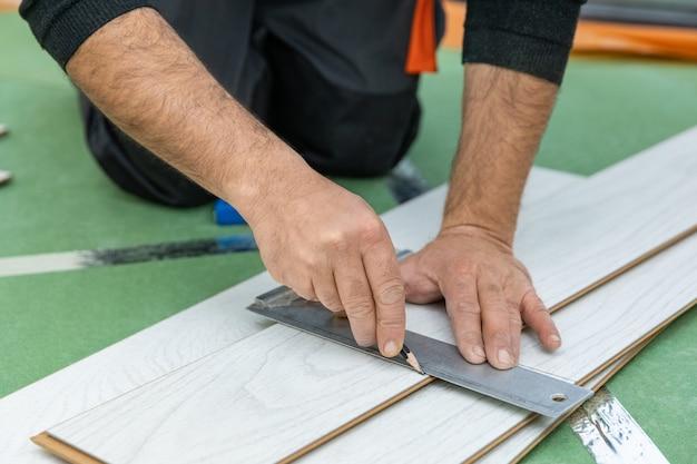 Pracownik mierzy długość białego laminatu drewnianego