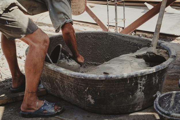 Pracownik mieszający tynk z zaprawy cementowej do budowy