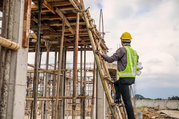 Pracownik młody profesjonalny inżynier w kask ochronny i papier plany pod ręką, pracując na drabinie na budowie budynku domu
