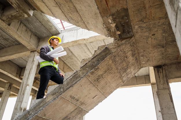 Pracownik młody profesjonalny inżynier w kasku ochronnym i papier plany pod ręką na budowie budynku domu