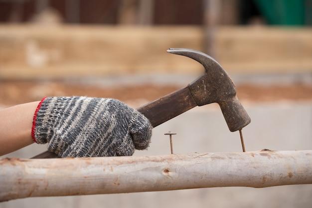 Pracownik młotkuje gwóźdź w drewno