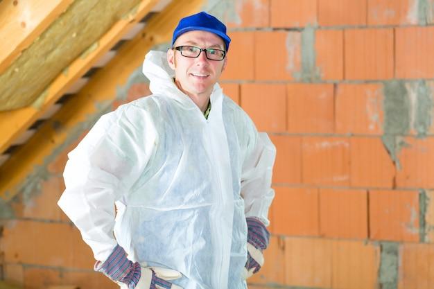 Pracownik mocujący izolację termiczną do dachu
