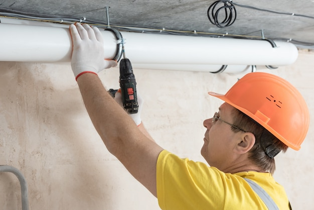 Pracownik mocujący rury wentylacyjne do sufitu za pomocą śrubokręta