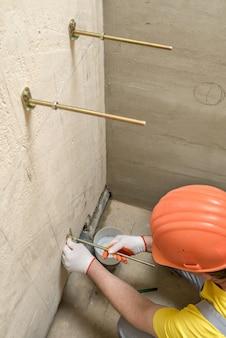 Pracownik mocujący ścianę ze śrub