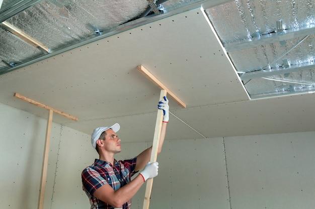 Pracownik mocujący sufit podwieszany.