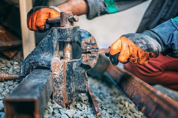 Pracownik mocuje metalową część w imadle przed cięciem, zbliżenie