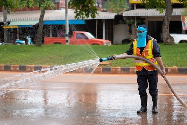 Pracownik mokre oczyszczenie ulicy z wodą pod ciśnieniem.