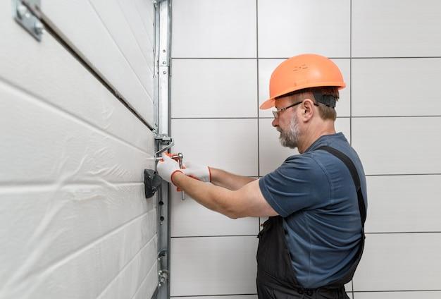 Pracownik montujący podnoszone bramy garażu