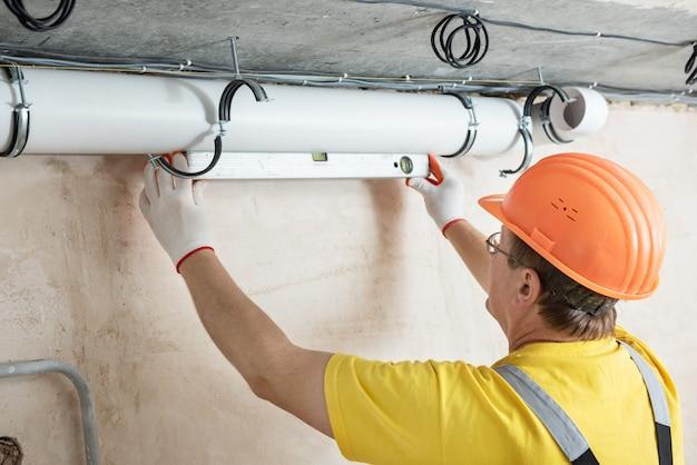Pracownik montujący system wentylacji w mieszkaniu
