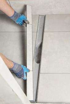 Pracownik montujący w łazience pokrywę ściekową ozdobioną płytkami ceramicznymi