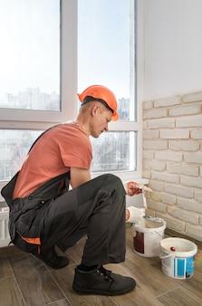 Pracownik montuje na ścianie płytki z cegły gipsowej.