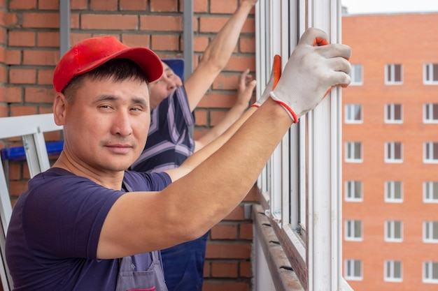 Pracownik montuje okna w wieżowcu