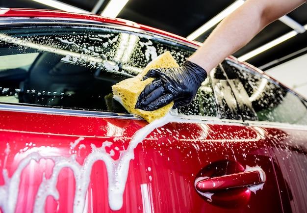 Pracownik myjący czerwony samochód gąbką na myjni samochodowej.