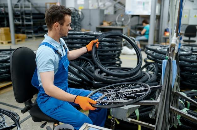 Pracownik na linii montażowej trzyma oponę rowerową w fabryce. produkcja kół rowerowych w warsztacie, montaż części rowerowych, nowoczesna technologia