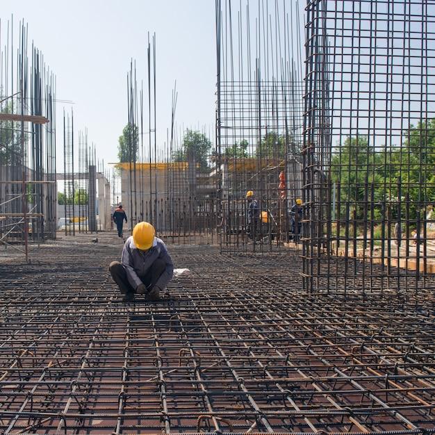 Pracownik na wzmacnia i łączy zbrojenie do wylewania fundamentu betonowego