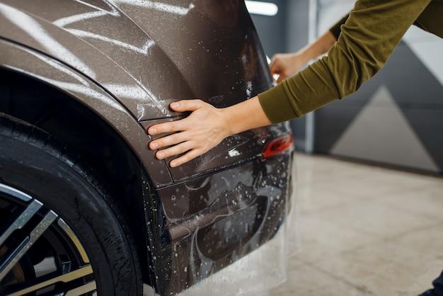Pracownik nakłada folię ochronną na tylny zderzak. montaż powłoki chroniącej lakier samochodu przed zarysowaniami. nowy pojazd w garażu, procedura tuningu
