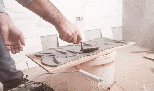 Pracownik nakładający klej na płytkę.