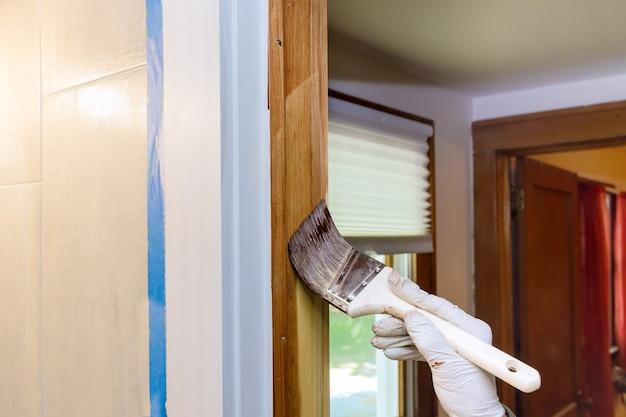 Pracownik nakładający lakier ochronny na drewniane drzwi za pomocą pędzla z listwami wykończeniowymi