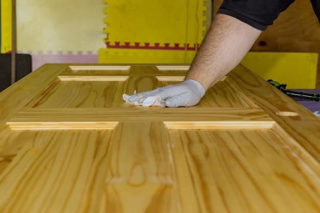 Pracownik nakładający lakier ochronny na drewniane drzwi za pomocą pędzla