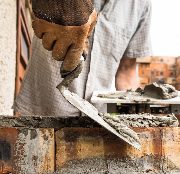 Pracownik nakładający zaprawę pacą na cegłę