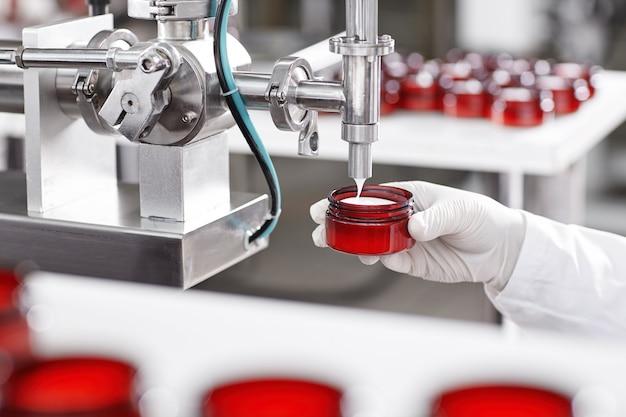 Pracownik napełniający pojemnik kremem w fabryce kosmetyków