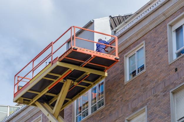 Pracownik naprawia elewację budynku mieszkalnego na koszu windy przemysłowej, widok od dołu