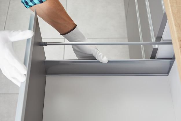 Pracownik naprawia mechanizm meblowy szuflady szafki