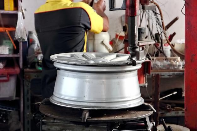 Pracownik naprawia zepsute koło w swoim garażu