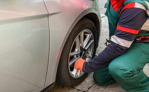 Pracownik naprawiający koło samochodowe za pomocą klucza z bliska