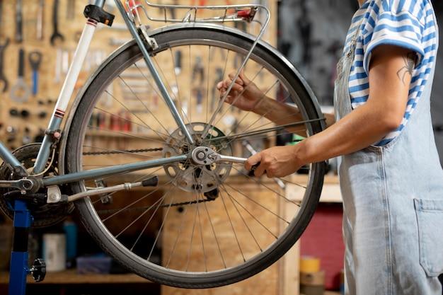 Pracownik naprawiający rower z bliska