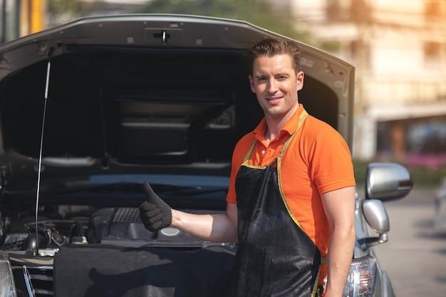 Pracownik naprawy człowiek polerowanie karoserii samochodu w garażu