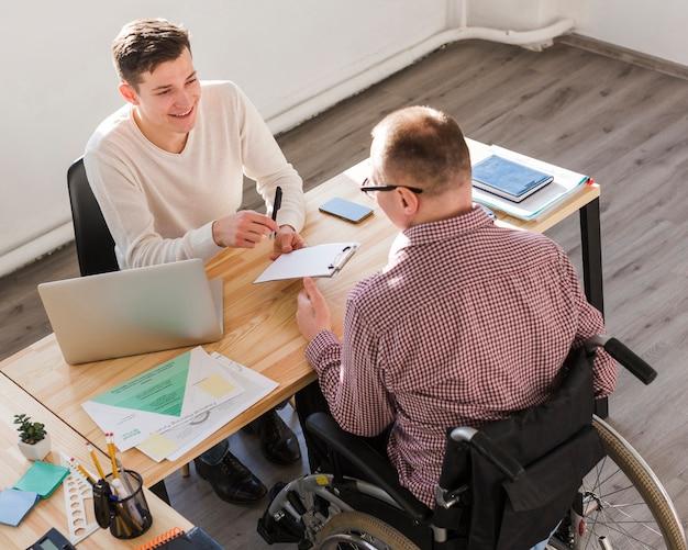 Pracownik niepełnosprawny wypełniający dokumenty do umowy