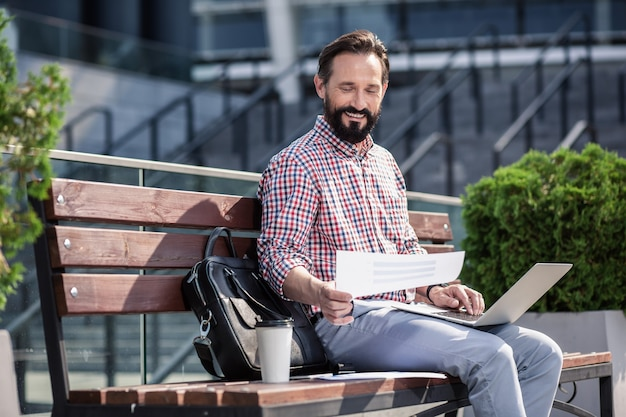 Pracownik niezależny. wesoły brodaty mężczyzna za pomocą swojego laptopa siedząc na ławce