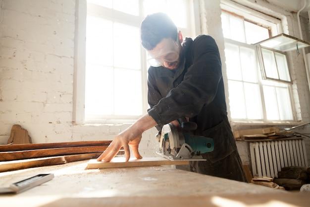 Pracownik obróbki drewna pracuje nad lokalną produkcją tarcicy