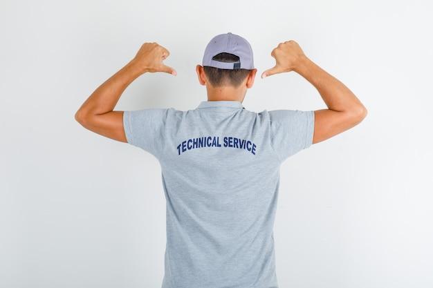Pracownik obsługi technicznej pokazujący tekst na mundurze w szarej koszulce z czapką
