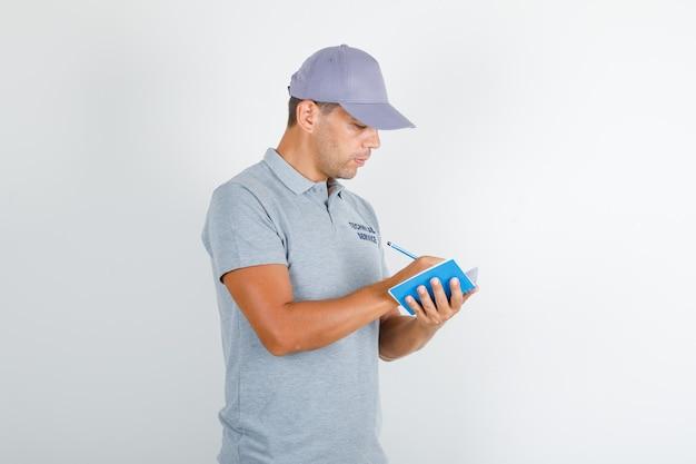 Pracownik obsługi technicznej robi notatki długopisem w szarej koszulce z czapką