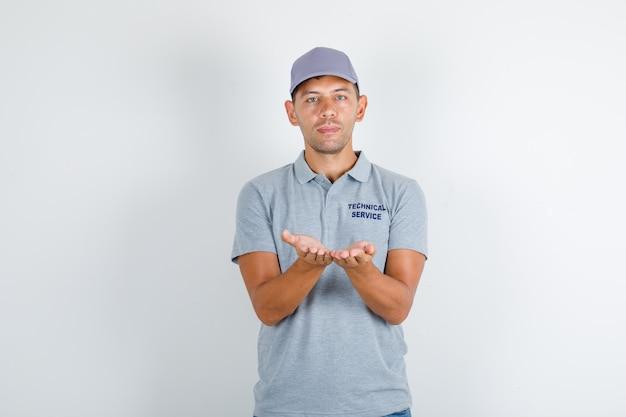 Pracownik obsługi technicznej trzymający otwarte dłonie w szarym t-shircie z czapką