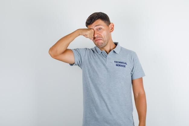 Pracownik obsługi technicznej w szarym t-shircie płacze jak dziecko i wygląda na zdenerwowanego